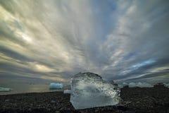 The ice floe on a black sandy beach Stock Photos