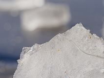 Ice floe at frozen lake surface with reflection stock photography