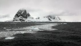 Ice floe in ocean of Antarctica. Glacier on background of snow mountains.Travel in calm cold polar north. Scenic blue water. Global warming. Unique nature of stock footage