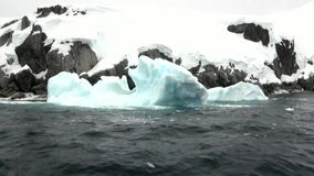Ice floe in ocean of Antarctica. Glacier on background of snow mountains.Travel in calm cold polar north. Scenic blue water. Global warming. Unique nature of stock video footage