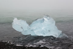 Ice floe in the ocean waves on the volcanic black sand beach, Iceland Royalty Free Stock Image