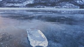 The ice floe rotates on the ice against the background of the amazing mountain landscape. Slow motion. The camera moves. Behind the ice. A piece of icy is very stock video