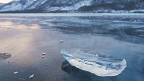 The ice floe rotates on the ice against the background of the amazing mountain landscape. Slow motion. The camera moves. Behind the ice. A piece of icy is very stock footage