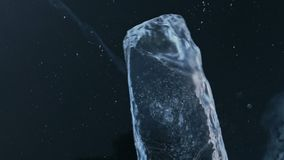 The ice floe rotates on the ice against the background of the amazing mountain landscape. Slow motion. The camera moves. Behind the ice. A piece of ice is very stock footage