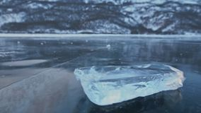 The ice floe rotates on the ice against the background of the amazing mountain landscape. Slow motion. The camera moves stock video