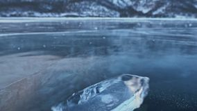 The ice floe rotates on the ice against the background of the amazing mountain landscape. Slow motion. The camera moves. Behind the ice. A piece of icy is very stock video footage