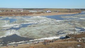 Ice floes float on the river in the spring during the ice drift. Floating ice floes on the river in the spring during the ice drift stock video