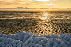 Ice floes floating on the fog water in the lake Baikal. Sunset Royalty Free Stock Photo