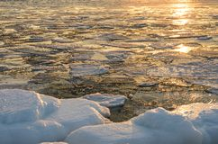 Ice floes floating on the fog water in the lake Baikal. Sunset Royalty Free Stock Image