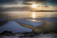 Ice floes floating on the fog water in the lake Baikal. Sunset. Ice floes floating on the fog water in the lake Baikal, Russia. Sunset Stock Photo