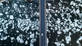 Ice floes floating on the river. River bridge. bird`s eye view royalty free stock photography