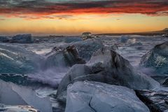 Ice floes on raging heavy sea at the shore of North Atlantic Ocean at the famous glacier lagoon in Vatnajokull National Park,. Raging heavy sea and winter storm royalty free stock image