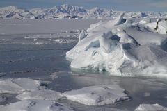 Ice floes and a small iceberg stuck in the ocean near a small is stock photo