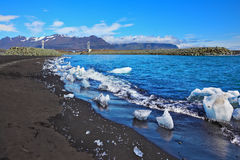 Ice floes in the sun shine. Ocean surf on the beach with black sand. Ice floes in the sun shine Stock Image