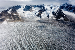 Ice flow divided around mountain top meeting to form beautifully textured pond Stock Photos