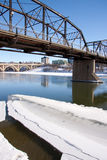 Ice flows on the River in Saskatoon. A view of the Victoria Bridge and Broadway Bridge in Saskatoon, Canada on a sunny day in winter royalty free stock photo
