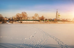 On the ice. Footprints in the snow and ice-covered river and the monastery on the other side Stock Images