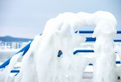 Ice formation on blue railing. Close up view of ice formation on bright blue pier railing Stock Photo