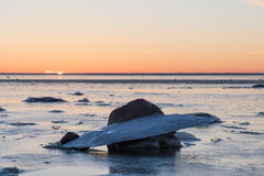 Ice formation by the coast. Ice formation at a rock by a beach at sunset royalty free stock photos