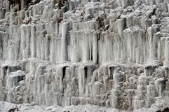 Ice Formations. Layers of ice formations on cliff in winter Stock Photo