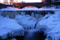 Ice formations and icicles on a river rapids in co Stock Photos