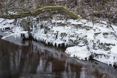 Ice formations at river bank. With icicles and reflection of them on water Royalty Free Stock Photography