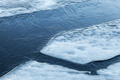 Ice fragments and thin layer of frozen river water Royalty Free Stock Images
