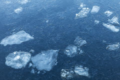 Ice fragments under thin layer of frozen river water royalty free stock photo
