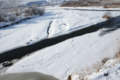 Ice-free mountain river in winter with animal trails Stock Photo