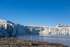 Ice front of Esmarkbreen glacier in Spitsbergen, sea, blue sky. Ice front of natural Esmarkbreen glacier in Spitsbergen, sea, blue sky royalty free stock photography