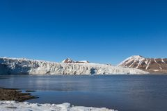 Ice front of Esmarkbreen glacier in summer, Spitsbergen, blue sky, sea. Ice front of natural Esmarkbreen glacier in summer, Spitsbergen, blue sky, sea royalty free stock photography