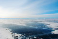 Ice of frozen dark-blue transparent waters of mountain lake. Thick ice of frozen dark-blue transparent waters; mountain lake in the morning frosty haze royalty free stock image