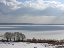 Ice frozen lake on a Sunny winter day in Russia. White snow and clouds in the blue sky. Beautiful winter landscape royalty free stock photos