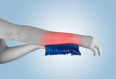 Ice gel pack on a swollen hurting wrist. Stock Images