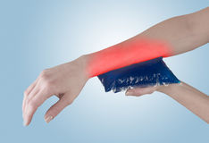 Ice gel pack on a swollen hurting wrist. Stock Photos