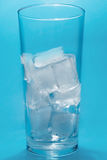 Ice in glass. On blue background stock photos