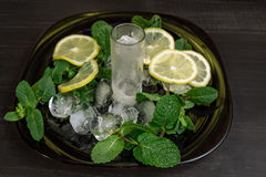 Ice glass and fresh mint with sliced lemon. With ice and mint in black plate on black table. Black Background. Texture royalty free stock image