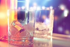 Ice in glass in nightlife with blurred background. Ice in glass in nightlife with colourful blurred background Stock Image