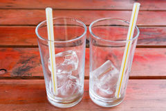 Ice in glass on rad wooden table Royalty Free Stock Photography