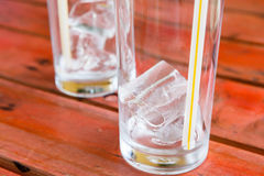 Ice in glass on rad wooden table Royalty Free Stock Image