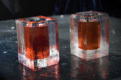 Ice Glasses. Two shot glasses made of ice filled with red drinks at an ice bar Stock Photo