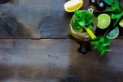 Ice green tea. Rustic kitchen table with glass mason jar of Ice green tea with lime, lemon, mint and ice cubes over old textured background. Copy space. Focus on Royalty Free Stock Photo