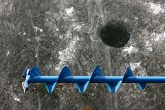 Ice. Hand ice auger and ice-hole on frozen lake Stock Image