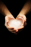 Ice heart. Concealing ice heart in hands Stock Photography