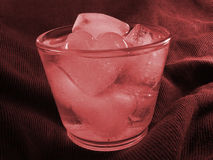 Ice heart. Glass of water with ice heart in red Royalty Free Stock Images