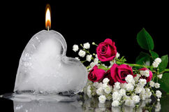 Ice heart melting with roses. Rose bouquet with flaming ice heart melting on a mirror Royalty Free Stock Photos