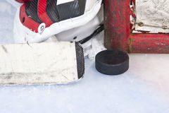 Ice Hockey. Close-up on hockey puck with goalie and net post stock images
