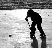 Ice hockey. Boy playing ice hockey with silhouette on outdoor rink Stock Photo