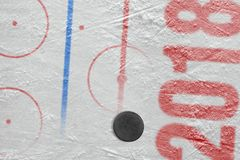 Ice arena and hockey puck Royalty Free Stock Images
