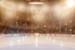 Ice Hockey Arena With Special Lighting Effects and Camera Flashe. Low angle view of fictitious hockey arena with sports fans in the stands. Focus on foreground stock photo